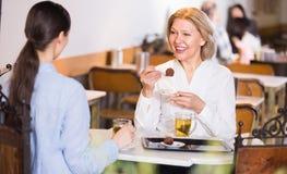 2 женщины с чаем и шоколадами Стоковое фото RF