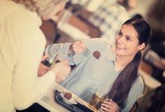 2 женщины с чаем и шоколадами Стоковая Фотография