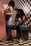 Женщины с электрической гитарой трястиют их головки в студии Стоковая Фотография RF