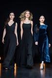 Женщины с ярким составом в стильных макси платьях идя совместно Стоковая Фотография