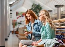 2 женщины с smartphone и хозяйственными сумками Стоковая Фотография