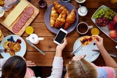 Женщины с smartphones есть еду на таблице Стоковое Изображение