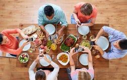 Женщины с smartphones есть еду на таблице Стоковая Фотография
