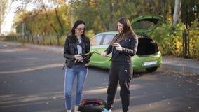 2 женщины танцуя около автомобиля с сломленным колесом с Джеком и руками видеоматериал