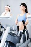 2 женщины тренируя на имитаторах в спортзале Стоковая Фотография RF