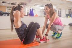 2 женщины тренируя спортзал разминки abs инструктора Стоковое Изображение RF