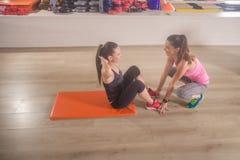 2 женщины тренируя спортзал разминки abs инструктора Стоковые Изображения