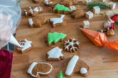 Женщины украшают печенье рождества в форме дома Стоковые Фотографии RF