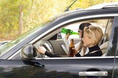 2 женщины управляя автомобилем пока выпивающ Стоковые Фотографии RF
