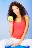 Женщины усаживая на голубой шарик pilates держа зеленое яблоко стоковая фотография