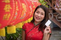 Женщины усмехаются карта шоу в красном платье фарфора стоковые фотографии rf