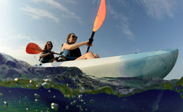 Женщины усмехаясь в голубом каяке на тропическом океане Стоковое Изображение