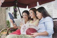 3 женщины усмехаясь и ослабляя с вентиляторами и таблеткой Outdoors Стоковые Фото
