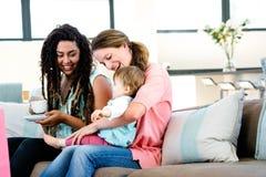 2 женщины усмехаясь на прелестном младенце Стоковые Фото