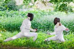2 женщины фехтовальщика рапиры воюя над красивой природой Стоковая Фотография