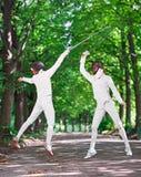2 женщины фехтовальщика рапиры воюя над переулком парка Стоковые Фотографии RF