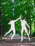 2 женщины фехтовальщика рапиры воюя над переулком парка Стоковые Изображения