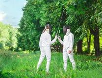 2 женщины фехтовальщиков оставаясь в парке с пересеченными рапирами Стоковые Изображения RF