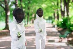 2 женщины фехтовальщиков рапиры оставаясь в переулке парка Стоковое Фото