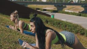 Женщины фитнеса делая планку работают в парке утра на циновке йоги в замедленном движении видеоматериал