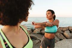 2 женщины фитнеса красоты протягивая ее руки outdoors Стоковые Изображения
