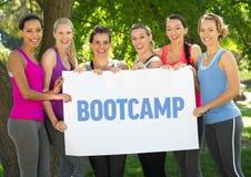 Женщины фитнеса проводят плакат с лагерем ботинка текста в парке стоковые изображения rf