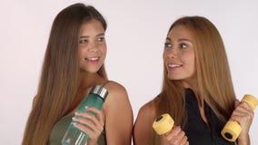 2 женщины фитнеса усмехаясь на одине другого, представляющ с бутылкой с водой и гантелями акции видеоматериалы