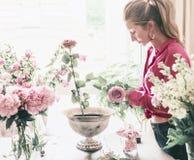 Женщины флориста с длинными светлыми волосами делают красивым большим праздничным событием классический букет с розами и другими  стоковые изображения