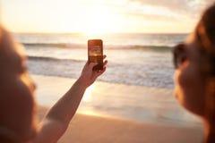 Женщины фотографируя заход солнца с умным телефоном на пляже Стоковое Изображение RF