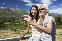 2 женщины фотографируя против загородки сельской местности Стоковые Изображения RF