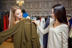 2 женщины ходя по магазинам выбирающ платья Красивые молодые покупатели в магазине одежды женщина ног принципиальной схемы мешка  Стоковая Фотография