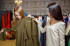 2 женщины ходя по магазинам выбирающ платья Красивые молодые покупатели в магазине одежды женщина ног принципиальной схемы мешка  Стоковая Фотография RF