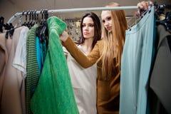 2 женщины ходя по магазинам выбирающ платья Красивые молодые покупатели в магазине одежды женщина ног принципиальной схемы мешка  Стоковые Изображения