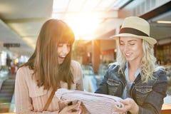2 женщины ходя по магазинам одежды на моле Стоковые Изображения