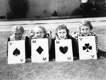 4 женщины хорошо подойдут для того чтобы лежать на траве с играя карточками перед ими (все показанные люди нет более длинного про Стоковые Изображения RF