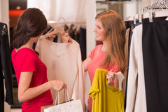 2 женщины ходя по магазинам выбирающ платья Стоковые Изображения