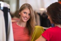 2 женщины ходя по магазинам выбирающ платья Стоковое Изображение RF