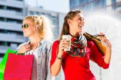 Женщины ходя по магазинам в городе с сумками Стоковые Фото