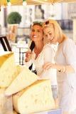 2 женщины ходя по магазинам для сыра на продовольственном рынке Стоковые Изображения