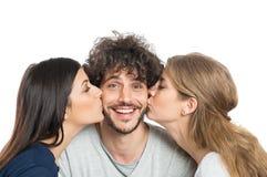 Женщины целуя человека на щеках Стоковые Фото