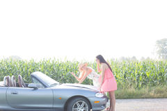 Женщины читая карту на автомобиле с откидным верхом на сельской местности Стоковая Фотография