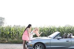 Женщины читая карту на автомобиле с откидным верхом на сельской местности Стоковое Изображение RF