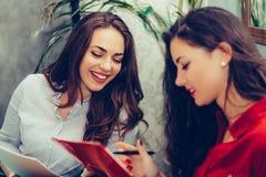 2 женщины читая печатные документы пока сидящ в таблице в кафе стоковые фото