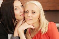 2 женщины шепча и усмехаясь Стоковое Фото