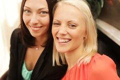 2 женщины шепча и усмехаясь Стоковые Изображения
