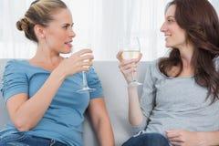 Женщины clinking их бокалы пока сидящ на софе Стоковые Фотографии RF