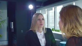 Женщины Coworking говоря в офисе 2 взрослых официально женщины в костюмах имея переговор в современном светлом офисе с лампой сток-видео