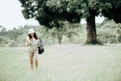 Женщины hiker или путешественник с картой удерживания приключения рюкзака для обнаружения направлений и идти для того чтобы ослаб стоковое изображение