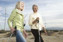 Женщины Hiking около ветровой электростанции Стоковая Фотография RF