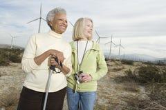 Женщины Hiking около ветровой электростанции Стоковая Фотография
